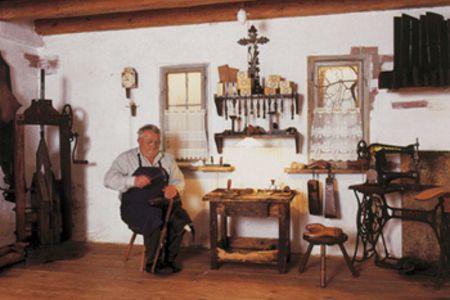 Ein Mann in einem alten Gebäude, der gerade Stiefel fertigt