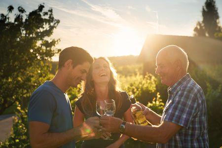 Lachende Menschen, die Wein verkosten im Sonnenuntergang