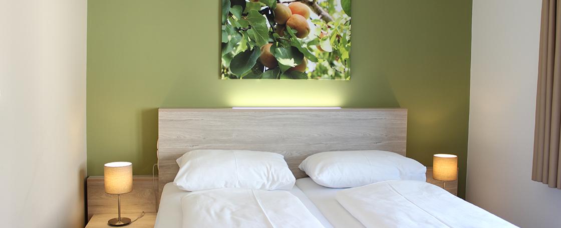 Doppelbett im Minihotel, grüne Wand und 2 Nachttischlampen brennen