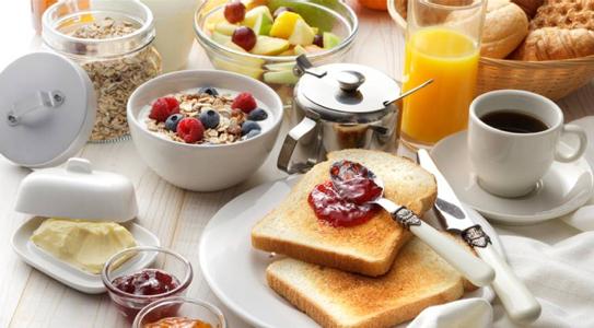 Frühstück: gedeckter Tisch mit Toastbrot mit roter Marmelade, Müsli, schwarzer Kaffee, Butter, Orangensaft und Obst