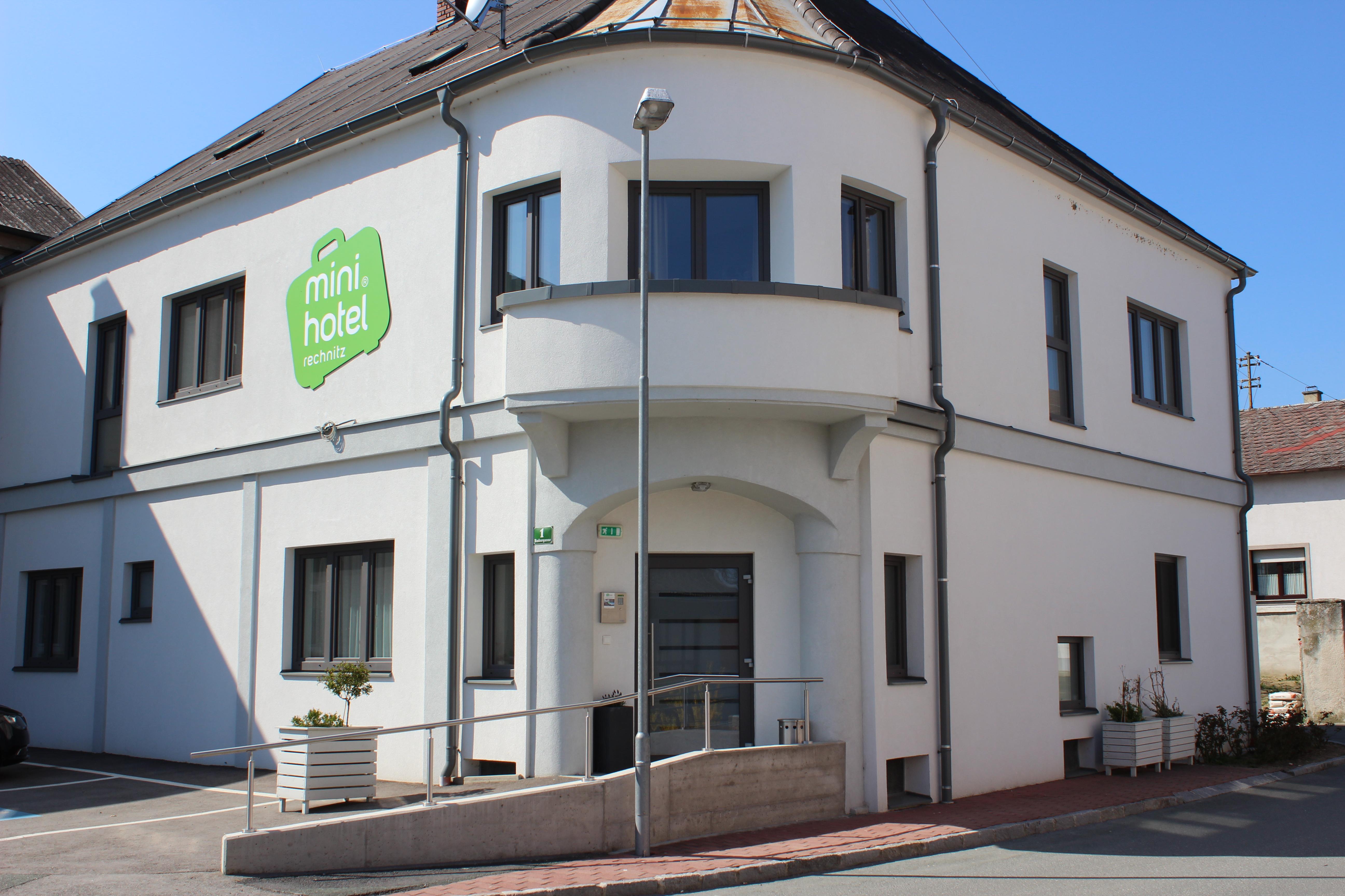 Eingangsbereich des Minihotels von außen mit grünem Logo auf Hausfassade