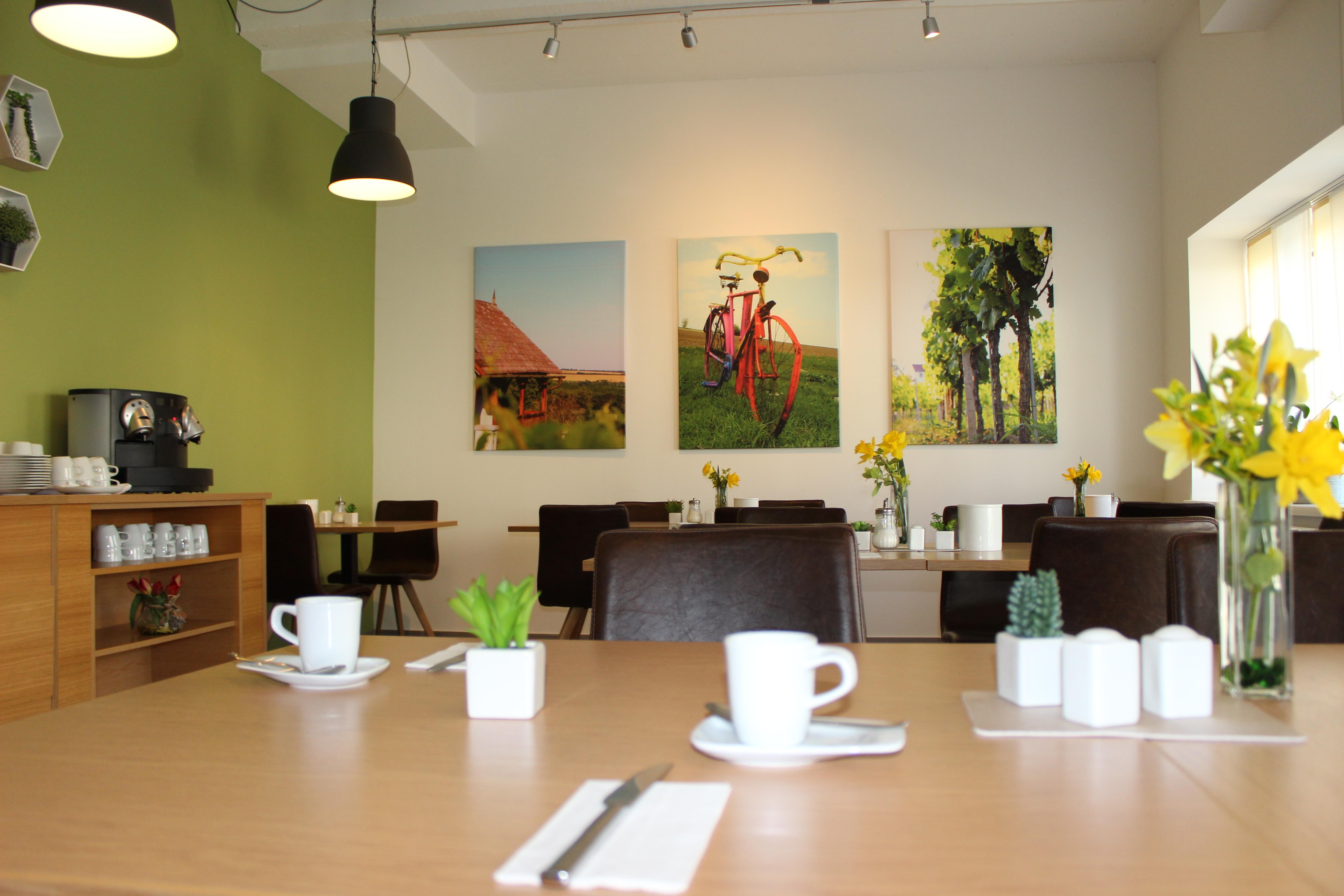 Frühstücksraum von innen, gedeckte Tische, Kaffeemaschine und Bilder an Wand