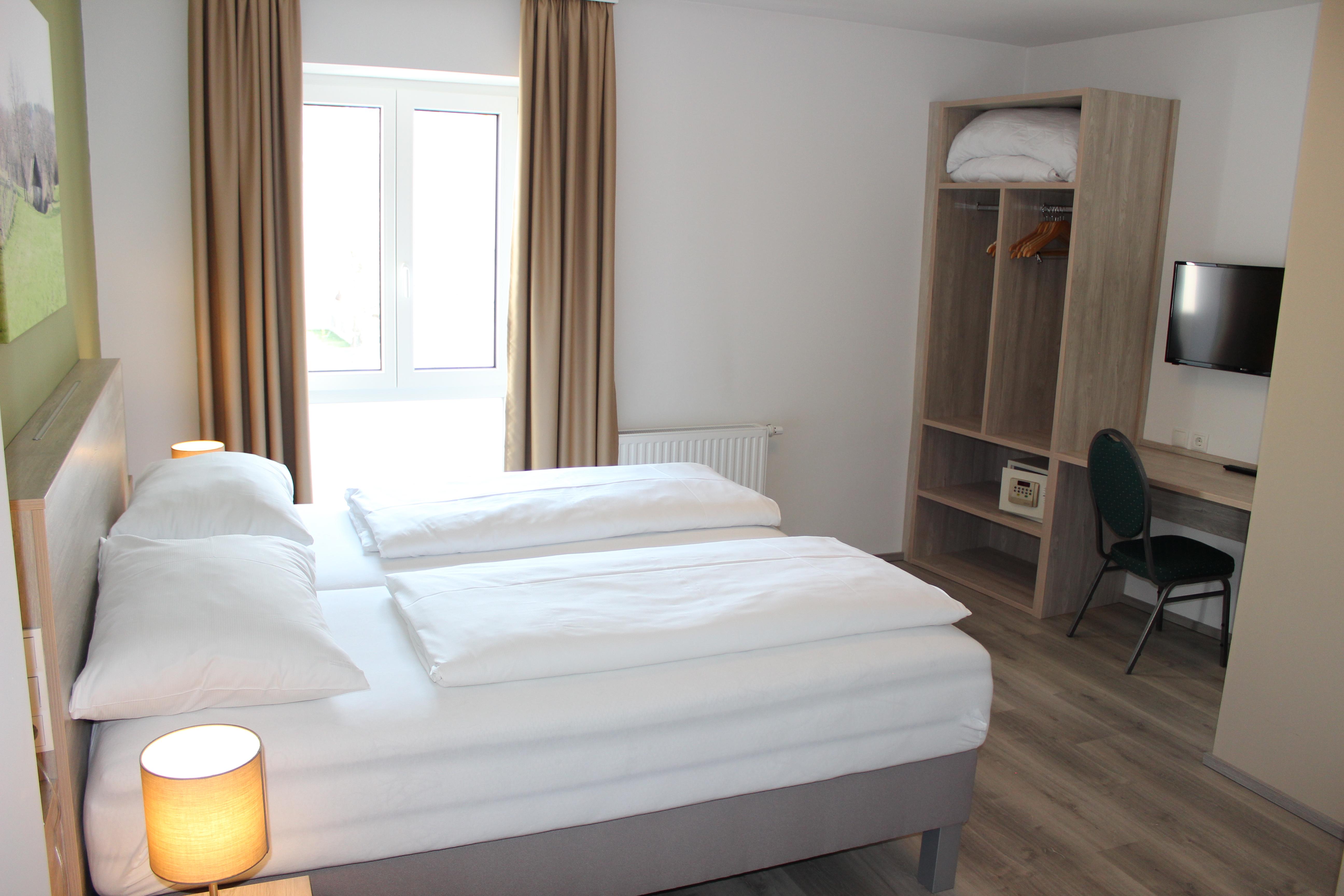 Doppelbett, Flachbildfernseher, Schreibtisch und Kleiderkasten