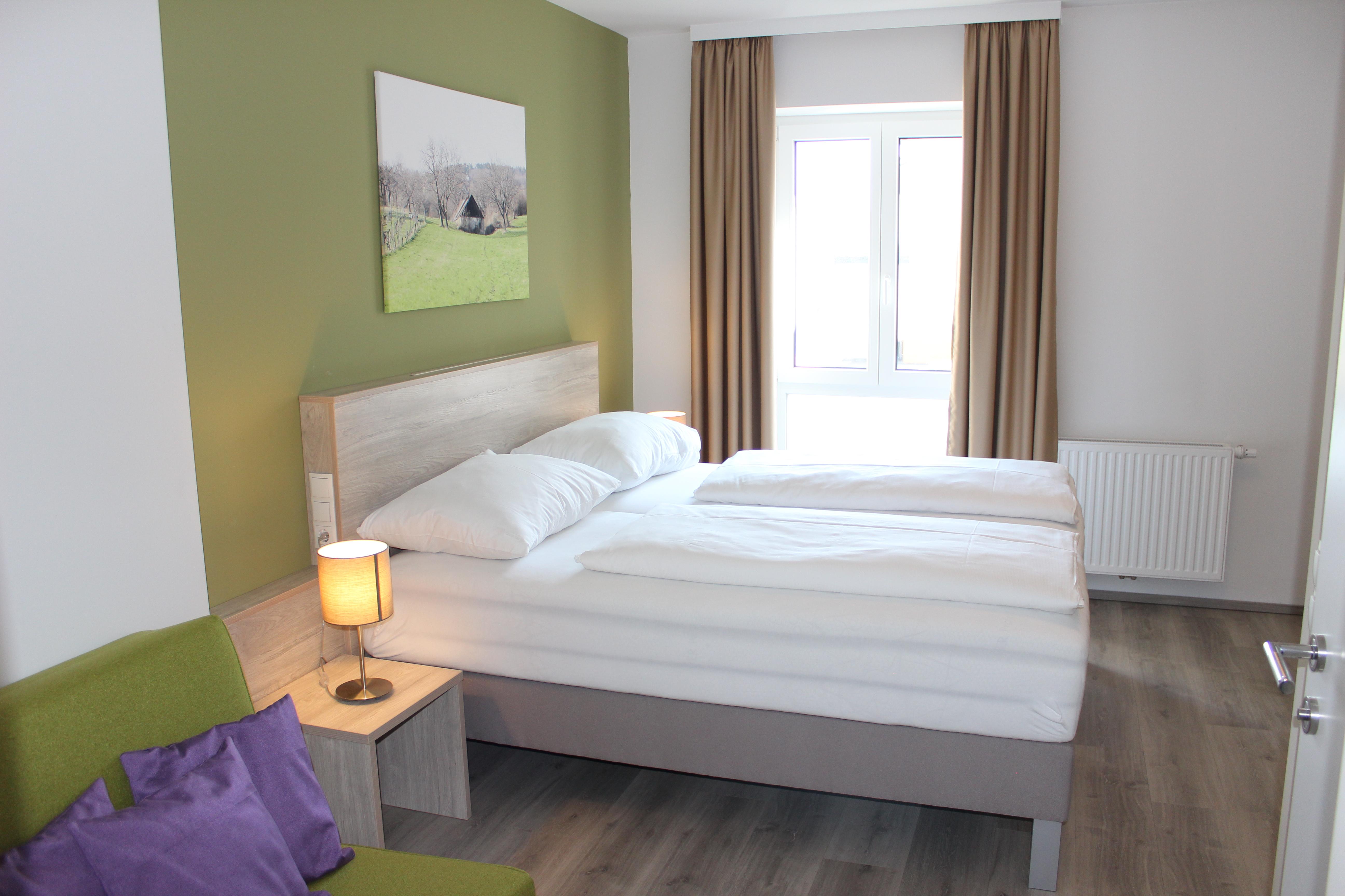 Doppelzimmer mit Doppelbett, grüner Wand und grünem Sessel mit lila Polstern