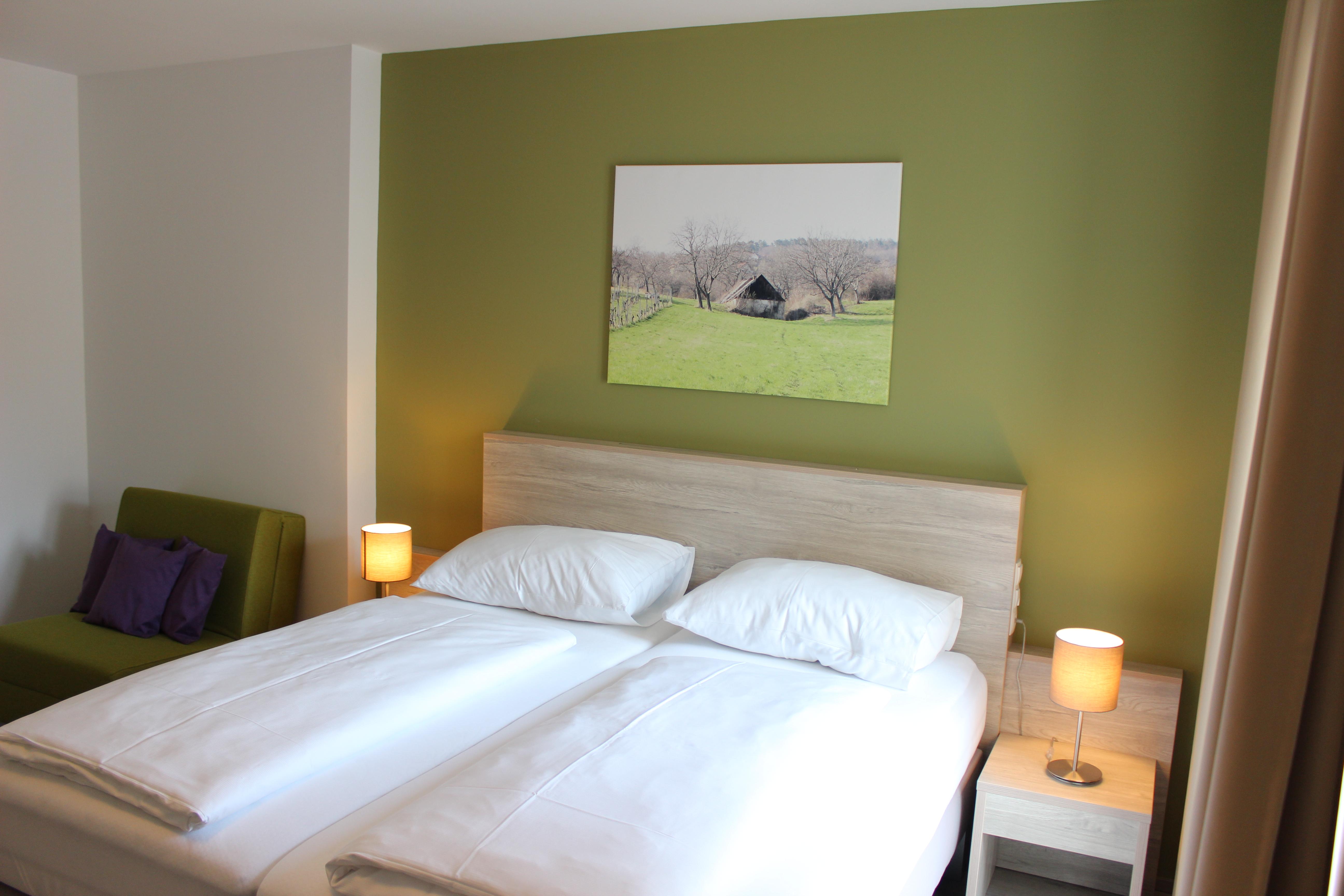 Doppelbett, Ansicht von vorne, Bild von Haus an grüner Wand