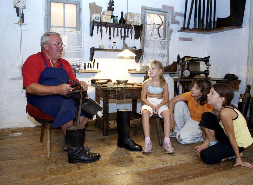 Ein Mann in einem alten Gebäude, der gerade Stiefel fertigt, drei Kinder schauen ihm zu